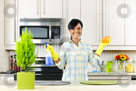Young woman cleaning kitchen stock photo, Smiling young black woman with sponge and rubber gloves cleaning kitchen by Elena Elisseeva