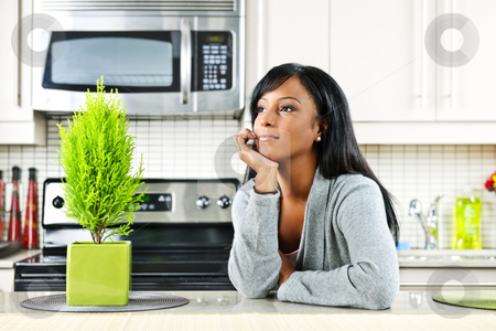 Thoughtful woman in kitchen stock photo, Thoughtful black woman in modern kitchen interior by Elena Elisseeva