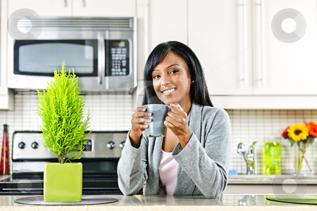 Woman in kitchen with coffee cup stock photo, Smiling black woman holding coffee mug in modern kitchen interior by Elena Elisseeva