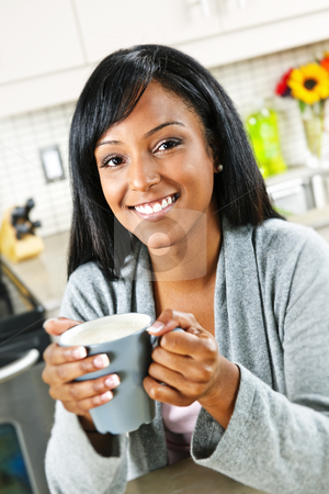 Woman in kitchen with coffee cup stock photo, Smiling black woman holding coffee cup in modern kitchen interior by Elena Elisseeva