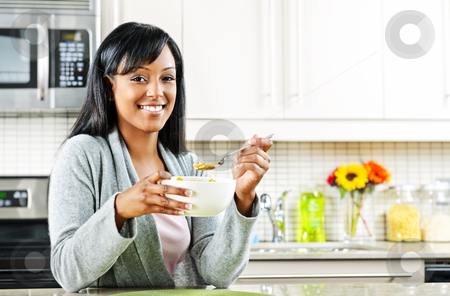 Woman having breakfast stock photo, Smiling black woman having breakfast in modern kitchen interior by Elena Elisseeva