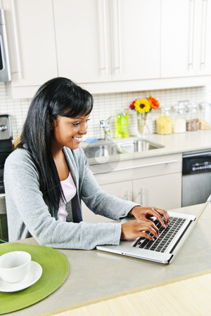 Young woman using computer in kitchen stock photo, Smiling black woman using computer in modern kitchen interior by Elena Elisseeva