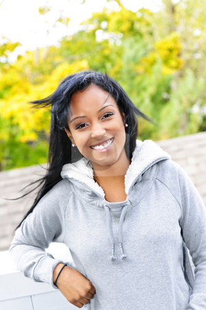 Portrait of young woman outdoors stock photo, Smiling young black woman outside in casual hoodie on windy day by Elena Elisseeva