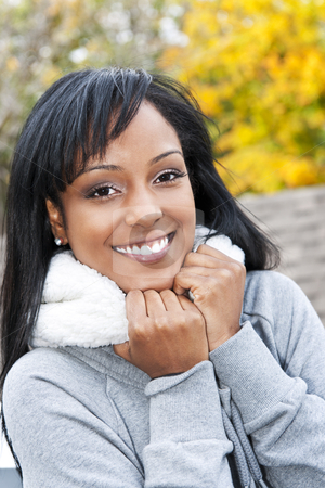 Portrait of young woman outdoors stock photo, Portrait of happy smiling young black woman outside in the fall by Elena Elisseeva