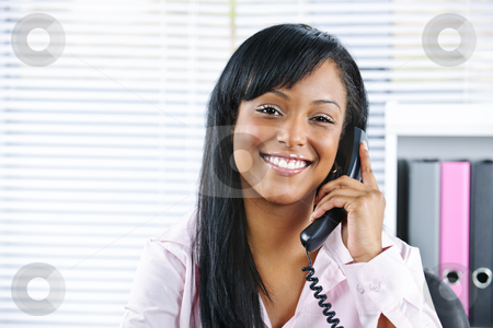Young black businesswoman talking on phone stock photo, Portrait of smiling black business woman on phone in office by Elena Elisseeva