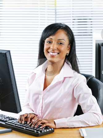 Happy black businesswoman at desk stock photo, Portrait of young smiling black business woman at desk typing on computer by Elena Elisseeva