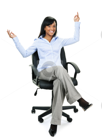 Happy businesswoman sitting on office chair stock photo, Young excited black businesswoman sitting in leather office chair by Elena Elisseeva