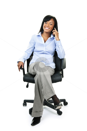 Businesswoman on phone sitting in office chair stock photo, Young smiling black businesswoman on phone sitting in leather office chair by Elena Elisseeva