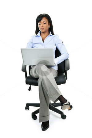 Woman sitting in office chair with computer stock photo, Young serious black woman sitting in leather office chair with laptop computer by Elena Elisseeva