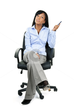 Thinking businesswoman sitting on office chair stock photo, Young black businesswoman sitting and thinking in leather office chair by Elena Elisseeva