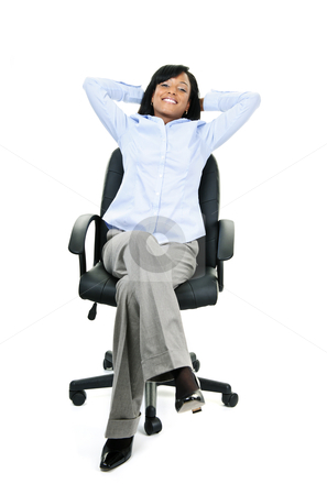 Relaxed businesswoman sitting on office chair stock photo, Young smiling black businesswoman relaxing sitting in leather office chair by Elena Elisseeva