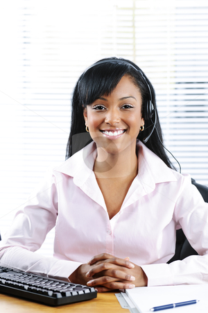 Customer service and support representative with headset stock photo, Smiling black customer service and support woman wearing headset at desk by Elena Elisseeva