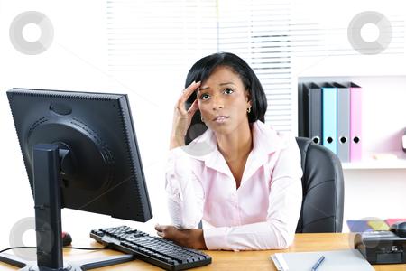 Worried black businesswoman at desk stock photo, Worried young black business woman at desk in office by Elena Elisseeva
