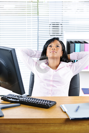 Black businesswoman resting at desk stock photo, Young black business woman resting at desk in office by Elena Elisseeva