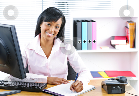 Smiling black businesswoman at desk stock photo, Smiling young black business woman writing at desk in office by Elena Elisseeva