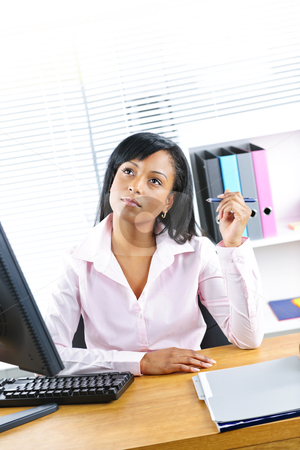 Black businesswoman working at desk stock photo, Young black business woman thinking at desk in office by Elena Elisseeva