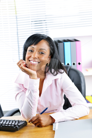 Black businesswoman at desk in office stock photo, Smiling young black business woman at desk in office by Elena Elisseeva