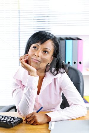 Black businesswoman at desk in office stock photo, Young black business woman thinking at desk in office by Elena Elisseeva