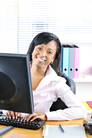 Happy black businesswoman at desk stock photo, Young smiling black business woman at desk typing on computer by Elena Elisseeva