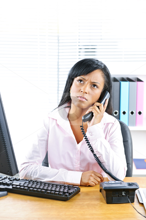 Concerned black businesswoman on phone at desk stock photo, Concerned young black business woman on phone at desk in office by Elena Elisseeva
