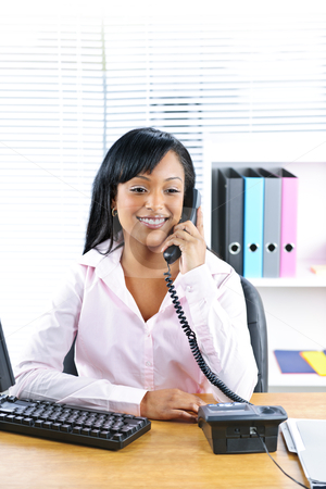 Smiling black businesswoman on phone at desk stock photo, Smiling young black business woman on phone at desk in office by Elena Elisseeva