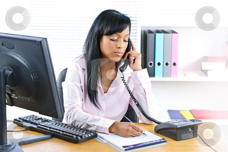 Serious black businesswoman on phone at desk stock photo, Serious young black business woman on phone taking notes in office by Elena Elisseeva