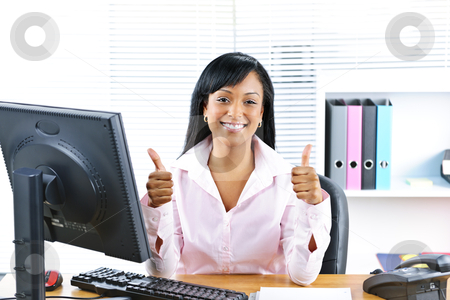 Businesswoman giving thumbs up stock photo, Smiling black business woman giving thumbs up gesture at desk in office by Elena Elisseeva