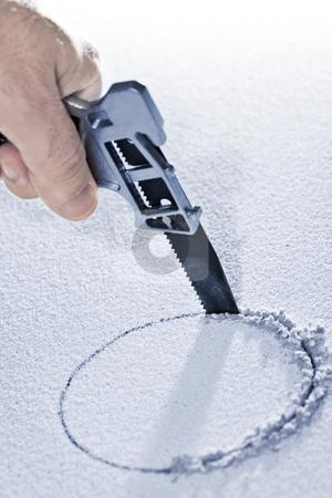 Saw cutting circular hole stock photo, Handsaw cutting circular hole in ceiling tile by Elena Elisseeva