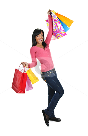 Excited young black woman with shopping bags stock photo, Young excited smiling black woman holding shopping bags by Elena Elisseeva
