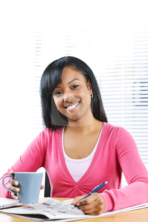 Young smiling woman looking for job stock photo, Happy young black female student looking in newspaper for job by Elena Elisseeva