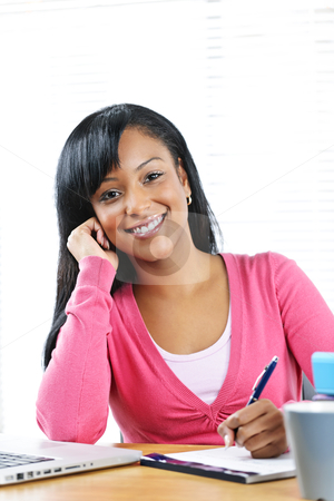 Happy female student studying stock photo, Portrait of smiling young black female student studying at desk by Elena Elisseeva