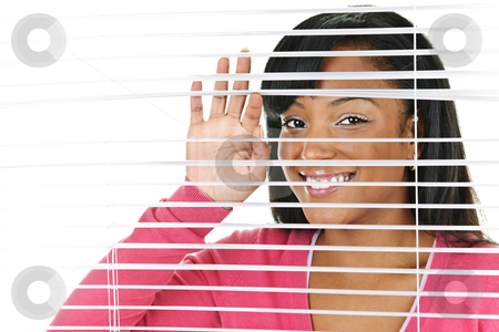 Smiling woman looking through blinds stock photo, Happy young black woman looking through horizontal venetian blinds by Elena Elisseeva