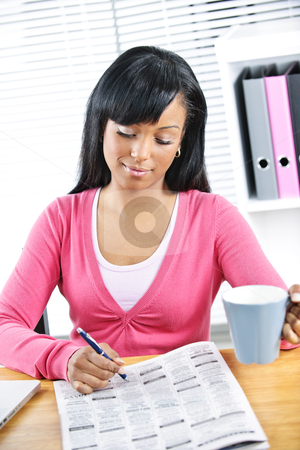 Young woman looking for job stock photo, Young black female student looking in newspaper for job by Elena Elisseeva