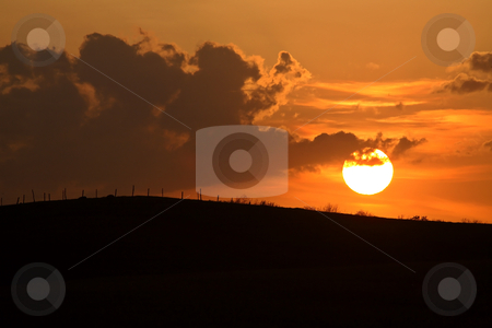 Sun setting behind a ridge in Saskatchewan stock photo, Sun setting behind a ridge in Saskatchewan by Mark Duffy