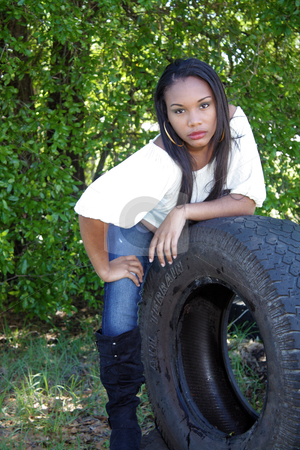 Beautiful Haitian Girl Outdoors (9) stock photo, A lovely young Haitian girl leans on a used all-terrain tire outdoors. by Carl Stewart