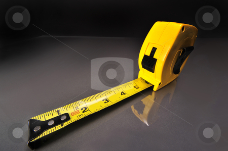 Tape Measure stock photo, Yellow tape measure on work table. by WScott