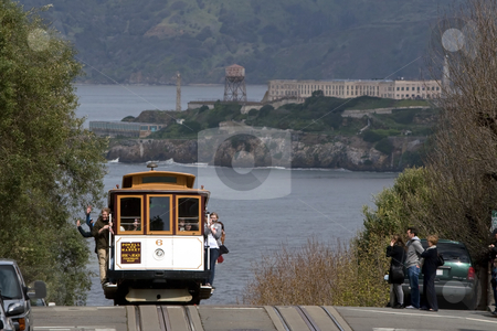 San Francisco Cable Car stock photo, San Francisco cable car on the top of the hill, passengers waving, with the view of Alcatraz in the background by mato020