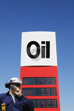 Oil-sign with engineer in foreground stock photo, engineer, worker talking in phone, large informative oil-sign in background, as seen inside the industry by lagereek