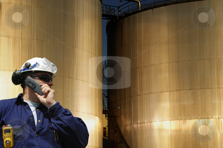 Oil-worker and industrial tanks stock photo, engineer, worker standing in front of sunlit industrial fuel-storage tanks by lagereek