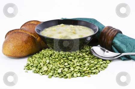 Country Split Pea Soup and Fresh Bread stock photo, Split pea soup in black bowl with fresh loaf of bread, green napkin and brown wood napkin ring on dried  peas ingredient against white background by Florence McGinn