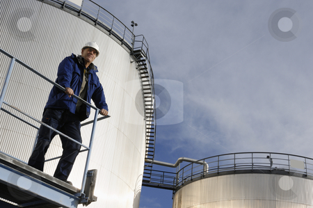 Oil-engineer and fuel storage stock photo, oil-worker, engineer, inspecting large industrial fuel-storage tanks by lagereek