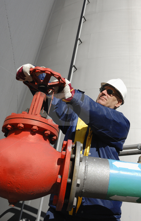 Oil-worker turning pipeline pumps stock photo, oil and gas worker, engineer, working inside oil and gas industry by lagereek
