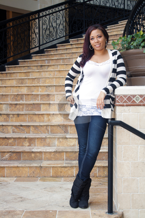Beautiful Casual Multiracial Girl stock photo, A lovely multiracial young woman in casual wardrobe stands relaxed at the bottom of a striking stairway. by Carl Stewart