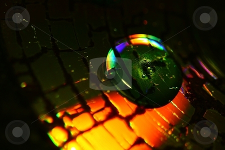 Abstract stock photo, a water drop on a cracked CD with bright colors by Karma Shuford