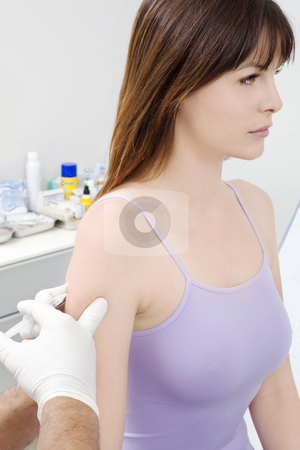 Young caucasian woman receiving a puncture from a doctor stock photo, young caucasian woman receiving a puncture from a doctor by ambrophoto