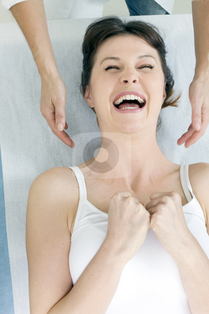 Young caucasian woman lying down smiling and receiving head massage stock photo, young caucasian woman lying down smiling and receiving head massage by ambrophoto