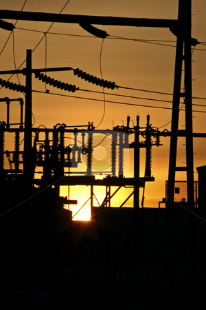 Sun setting behind electric station stock photo, Sun setting behind electric station by Mark Duffy