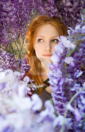 Spring beauty among flowers. stock photo, Romantic portrait of beautiful young redhead girl among spring lilac flowers. by exvivo