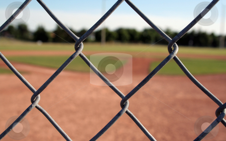 Through the Links stock photo, A view of a baseball diamond behind the fench with the chains links in focus. by Chris Hill
