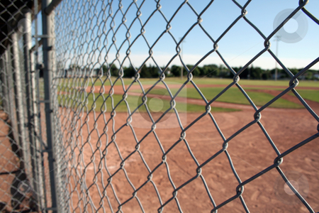 Behind the Fence stock photo, A view from behind the fence at a small baseball field.  by Chris Hill